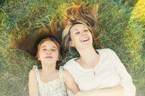 happy little girl and her mother having fun outdoors on the green grass in sunny summer day